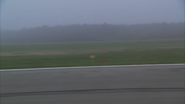process plate straight left from airplane on runway. could be about to take-off. small private propeller planes in bg. grass fields. republic airport, east farmingdale, long island, new york. overcast sky. fog. - runway stock videos & royalty-free footage