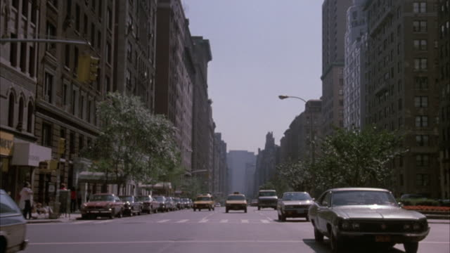 process plate rear pov of car driving in new york city. sides of street lined with tall buildings and parked cars. several cars on road behind car. yellow taxi directly behind camera for entire shot. - anno 1987 video stock e b–roll