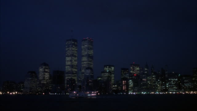 WIDE ANGLE OF NEW YORK CITY SKYLINE. WORLD TRADE CENTER VISIBLE IN SHOT. FERRY BOAT, POSSIBLY STATEN ISLAND FERRY, CAN BE SEEN MOVING FROM RIGHT TO LEFT OFF SCREEN. TWIN TOWERS. NEW YORK HARBOR. SKYSCRAPERS.