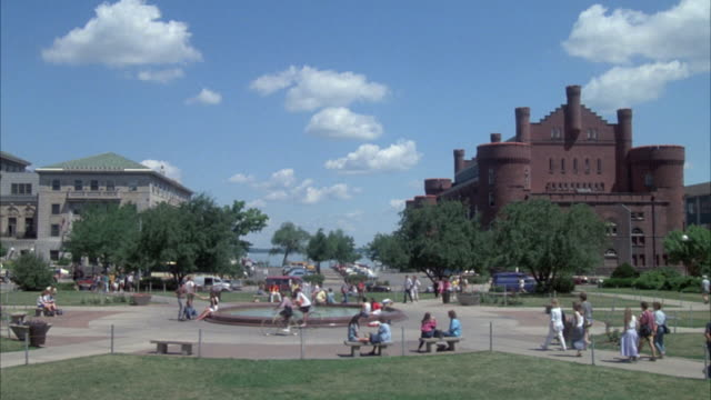 medium angle of plaza and fountain at university of wisconsin, madison. students, pedestrians pass by. student union building on left, and red brick armory on right. lake visible in bg. college campus. - midwest usa stock videos & royalty-free footage