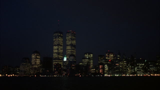 vídeos de stock e filmes b-roll de panoramic establish of new york city skyline. see twin towers at center. see city lights and lit office lights. pov is from ocean. see lights on top of some buildings flashing. - world trade center manhattan