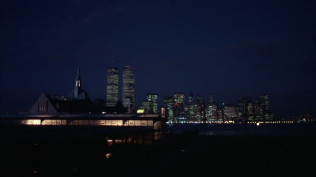 wide angle of warehouse with lit windows. see steeple behind. see new york city skyline in background. see twin towers. see boats crossing through water. - steeple stock videos & royalty-free footage