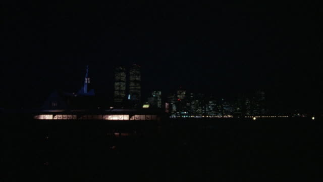 wide angle of warehouse with lit windows. see steeple behind. see new york city skyline in background. see twin towers. see boats crossing through water. very dark. - steeple stock videos & royalty-free footage