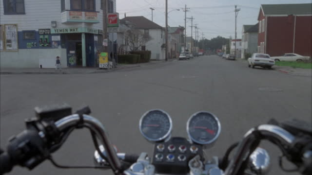 process plate of off screen person riding motorcycle down city streets. see handle bars and speedometer. see townhomes and parked cars on sides. see little boy standing on corner where motorcycle turns. see a semi truck pass on the left. see a junk yard a - speedometer stock videos & royalty-free footage