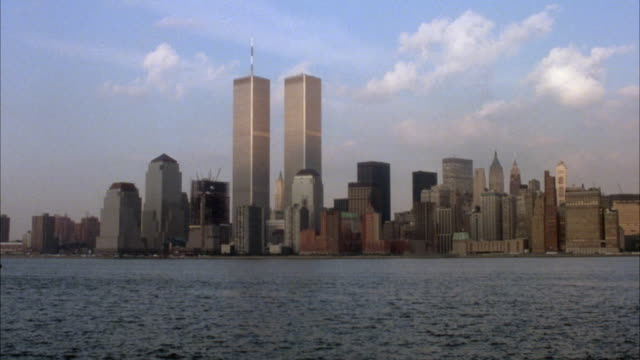 panoramic establish of new york city skyline. see twin towers at center. see clouds in background. pov is from ocean. - world trade center manhattan stock videos & royalty-free footage