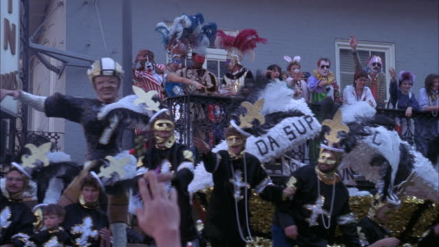 "medium angle of mardi gras parade.  see float with sign ""please jim, mor-a this""  going by.  float riders  wearing new orleans saints  jerseys.  partiers watch from balcony.  lots of feathers and masks.  people throwing beads. - new orleans mardi gras stock videos and b-roll footage"