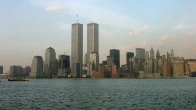 panoramic establish of new york city skyline. see twin towers, world trade center skyscrapers at center. pov is from new york harbor. - 1982 stock videos and b-roll footage
