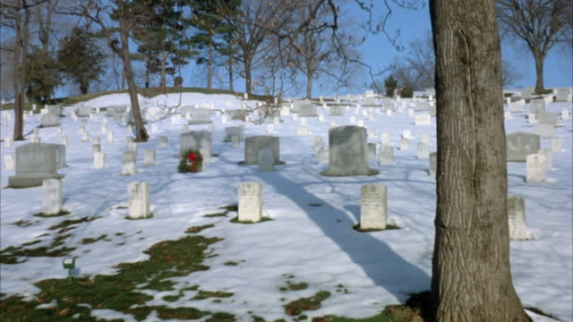 vidéos et rushes de wide angle of arlington national cemetery. snow on ground. wreath on one headstone. see military funeral procession with horses drawing caisson in far background. - cimetière militaire d'arlington