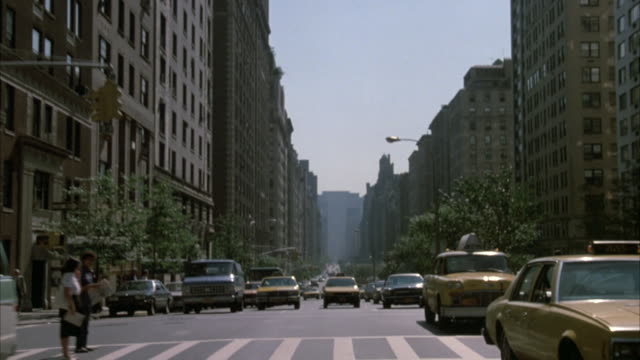 vidéos et rushes de process plate rear window or mirror pov driving down park avenue. see several yellow taxis on driver side. many cars parked on passenger side. tall high rise buildings line both sides of street. see bicyclist riding down street on passenger side. - yellow taxi