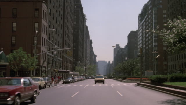 vidéos et rushes de process plate rear window or mirror pov driving down park avenue. see several yellow taxis on driver side. many cars parked on passenger side, several double parked. tall high rise buildings line both sides of street. - yellow taxi