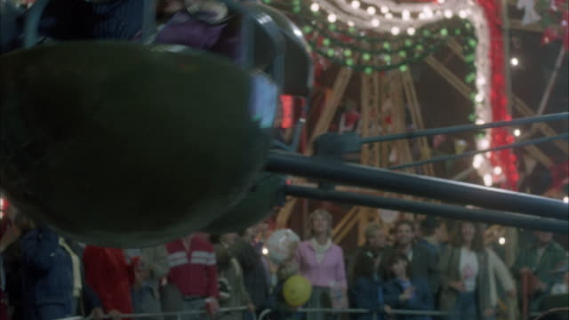 vidéos et rushes de medium angle of children riding carnival ride around in circles in mini-cars with steering wheels. parents are visible in background and there are many carnival lights and balloons in background. - fête foraine