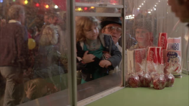 medium angle of concession stand from inside with candy apples, popcorn, and drinks in clear view. people purchase popcorn and cotton candy from vendor who hands it to them through window. possibly pov of concession stand worker. - 1982 stock videos and b-roll footage