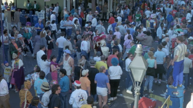 stockvideo's en b-roll-footage met high angle down of mardi gras celebration with people dressed in costumes, masks and party hats. see people mill around intersection. see man standing on boxes at right. see tiki torch in foreground. - tiki torch