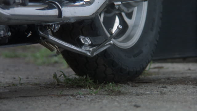 close angle of foot standing by motorcycle  kickstand. foot is wearing black leather boot. see chrome exhaust pipe and tire of motorcycle in background. then see boot kick down kickstand and stand next to motorcycle. neg cut. - motorradfahrer stock-videos und b-roll-filmmaterial