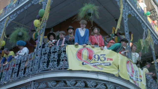 "up angle of people standing on balcony in costume or wearing party hats. see banner for ""q93 fm - continuous music"" on balcony. pans right to adjacent buildings. - new orleans mardi gras stock videos and b-roll footage"
