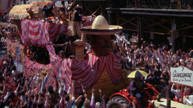 "medium angle of mardi gras parade from left to right. tractor with sign reading ""7 governor"" leads large parade car with head figure wearing mexican sombrero. parade car has three levels of dozens of men in sombreros throwing objects to crowd. zoom in on - new orleans mardi gras stock videos and b-roll footage"