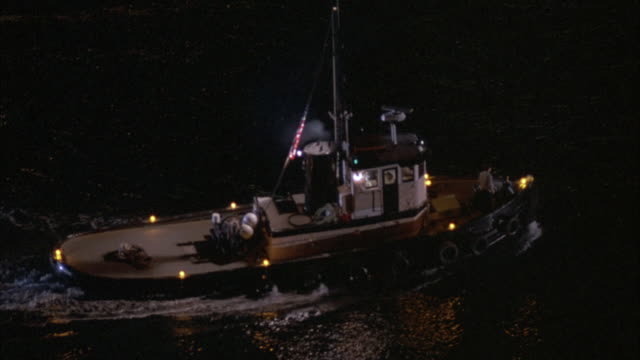 vidéos et rushes de medium angle of patrol tugboat on river by new york city. boat has blue light, spinning radar reader, and american flag on pole. person stands on deck or front. boat curves and moves right. river water ripples and reflects lightning. - remorqueur