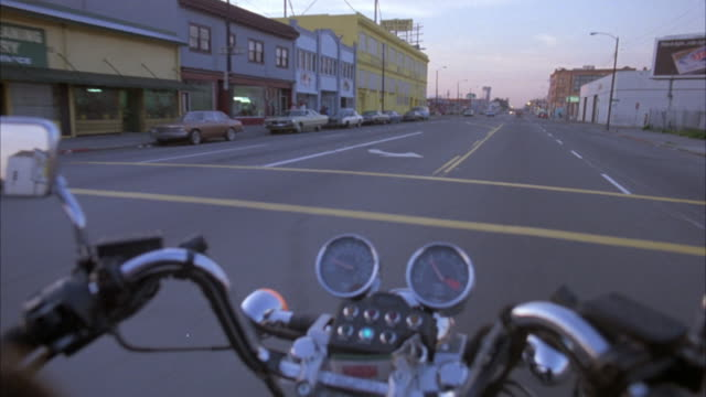 "3/4 forward process plate, moving pov on motorcycle. view of handles, back mirrors, gauges of motorcycle in front center. sign reads ""bell's dry cleaning & laundry"", cars parked by street, and yellow building reads ""economy self storage"". some cars on opp - self storage stock videos and b-roll footage"