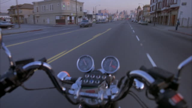 3/4 forward process plate, moving pov on motorcycle. view of handles, back mirrors, gauges of motorcycle in front center. blue buick sedan on left lane. motorcycle passes buick and focuses on seven people in front of town house and turns right to alley. h - motorcycle biker stock videos & royalty-free footage