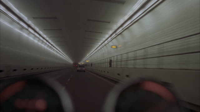7/8 front process plate, motorcycle pov through urban tunnel.  motorcycle gauge in front center. enters and swerves in tunnel and avoids traffic. tunnel has two parallel lines of lights on each side of ceiling. exits tunnel on upward ramp. - meter instrument of measurement stock videos & royalty-free footage