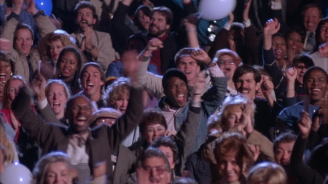 medium angle of crowd in auditorium cheering. red, white and blue balloons. men, women, teenagers. clapping. celebrations. preview file has been trimmed from master clip 6030-021. for additional footage, see clip 6030-901. full clip available by calling s - auditorium stock videos & royalty-free footage