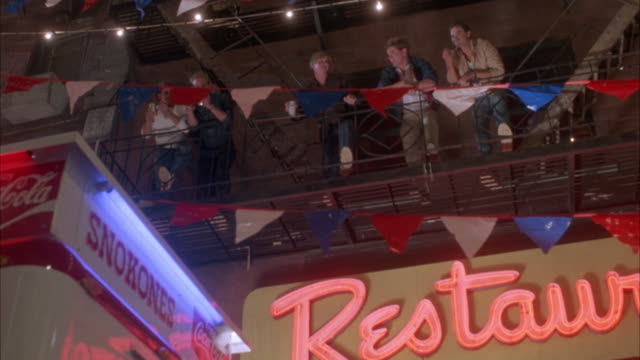 """up angle of five young men on fire escape at carnival. men are looking down, shouting at people passing by below. see signs in foreground reading """"snokones"""", neon sign of """"restaurant"""", and coca-cola ad. three horizontal lines of small red, white and blue - 非常階段点の映像素材/bロール"""
