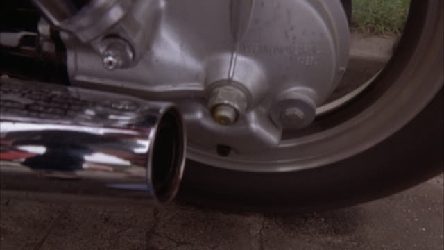close angle of rear wheel of motorcycle rotating in place. chrome exhaust or pipe or muffler on left. see some engine exhaust at end. insert. - motor stock-videos und b-roll-filmmaterial