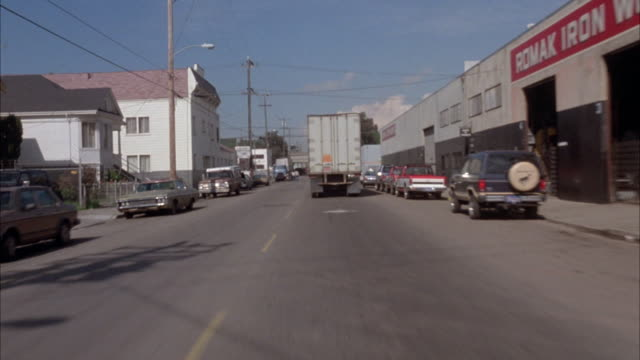 "7/8 front process plate of town street, moving pov on motorcycle. shot turns to slight left passing by town house on corner. moving van ahead, pick-up truck passes by on opposite side. parked cars, and houses on sides, pass by sign reading ""romak iron wor - oakland california stock videos & royalty-free footage"