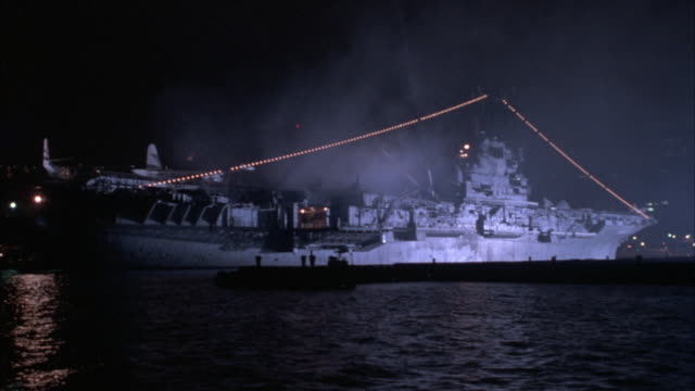 wide angle of u.s. navy aircraft carrier,  ship in harbor. string of lights spans over ship from  front to back. steam or smoke visible,  spotlights blaze from center of ship. - us navy stock videos and b-roll footage