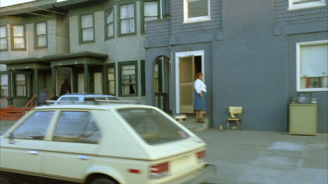 7/8 front process plate, moving pov on motorcycle in residential area on right. women leaves blue house and two people enter green house next to blue house. pass by parked vintage cars, vw volkswagen mini-van and light brown sedan. - oakland california stock videos & royalty-free footage
