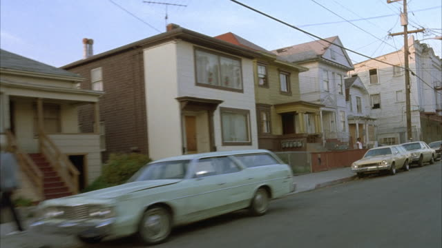 3/4 front process plate, moving pov on motorcycle in residential area on left. houses and people on sidewalk, in front of houses and near parked cars. street connects to main street across. ends at sidewalk curb. - oakland california stock videos & royalty-free footage