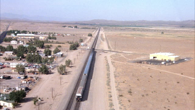 high level aerial of train on railroad in desert heading north. train has thirteen cars. mountains in distance. shrubs, electric wires and trees scattered around. small town on sides of rails. - 1982 stock videos and b-roll footage