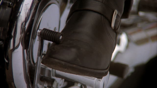 3/4 side close angle of motorcycle brake pedal and clutch. black leather boot adjusts clutch, lifts up and steps on clutch. insert. - pedal stock videos & royalty-free footage