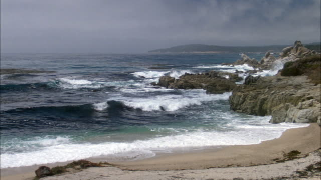 medium angle of waves breaking on beach shore. rocks or low beach cliffs on right. white sand beach in foreground, hill in distance. water is blue and green. sky is cloudy or overcast. point lobos.preview file has been trimmed from master clip 6031-002. f - carmel california stock videos & royalty-free footage