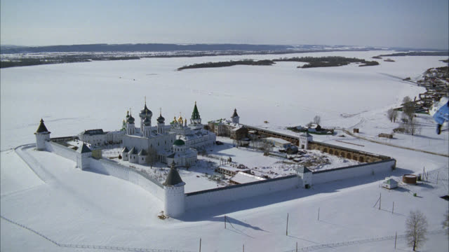 aerial of makariev monastery near nizhny novgorod on the volga river. could be fortress, castle, convent, russian orthodox church or cathedral. snow. walls with guard towers, turrets. onion domes. helicopter flies over russian countryside or rural area. m - festung stock-videos und b-roll-filmmaterial