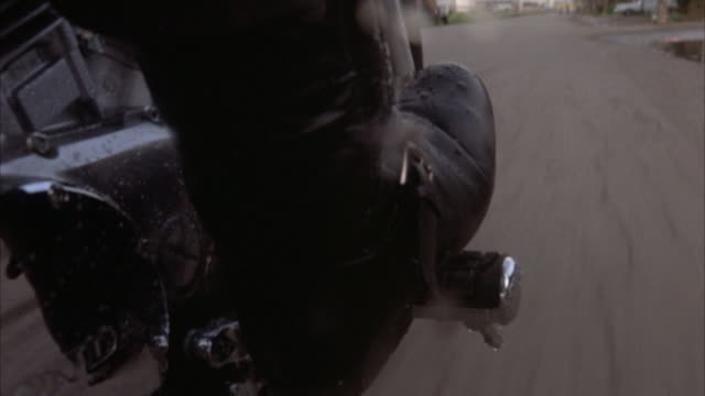 close angle front 3/4 moving pov on motorcycle, see side of motorcycle pedal and black leather boot. road moving on right side. motorcycle turns right, boot steps on clutch and adjusts speed. passes puddle and splashes water on boot and motorcycle. insert - motorcycle biker stock videos & royalty-free footage
