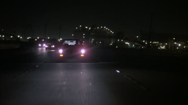 straight back process plate of cars on 405 freeway near carson city. headlights, street lights, opposite traffic, and factory with many light on left of freeway.  cars go up and down ramp. - kalifornien stock-videos und b-roll-filmmaterial