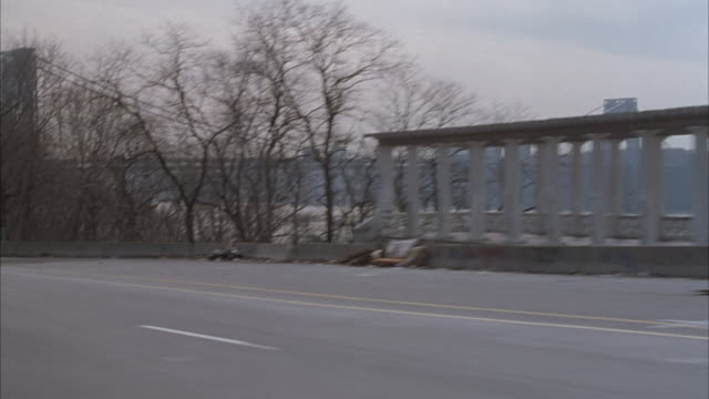 process plate 3/4 back driver side on highway, cars pass pov. river next to highway, high rise buildings across river in background. trees on bank of river. preview file has been trimmed from master clip 6211-036. for additional footage, see clips 6211-90 - anno 1994 video stock e b–roll