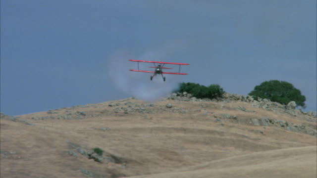 MEDIUM ANGLE TRACKING SHOT OF RED BIPLANE IN DESERT. BIPLANE APPEARS FROM BEHIND SAND HILL FLIES OVER BARN AND FLIES TO LEFT. SEE PLANE EXHAUST.