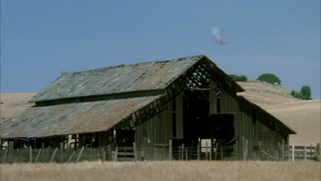 CLOSE ANGLE OF BARN ON DESERT. RED BIPLANE FROM DISTANCE OVER SAND HILL APPROACHES BARN FROM BACK.
