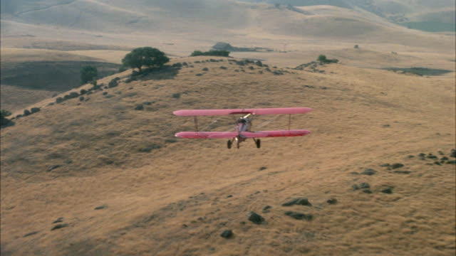 medium angle aerial of plains on hills or mountains. red biplane in foreground, moving pov swerves left and right above plains, hills, see animals or livestock within fence of barn. swerve above barn to right. plane exits to right. - 複葉機点の映像素材/bロール