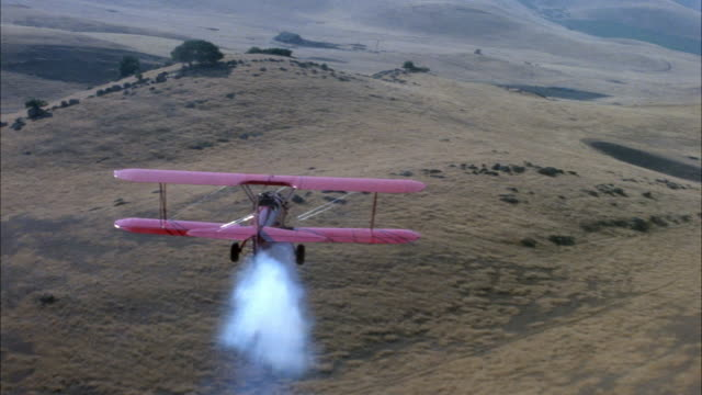 medium angle aerial of plains on hills or mountains. red biplane in foreground, moving pov swerves up and down above plains, hills, see barn in distance.  swerve above barn to right. plane exits to right. - 複葉機点の映像素材/bロール