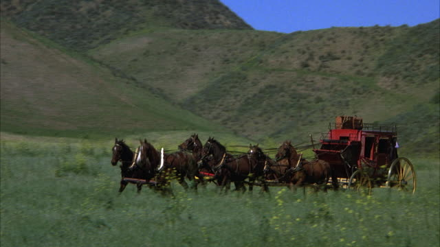 vidéos et rushes de medium angle of meadow with grass and hills in background. six-horse drawn carriage appears from right, shot follows to left. carriage is red, and two pieces of luggage on roof, person in carriage opens and closes carriage door. carriage exits to left. - voiture attelée