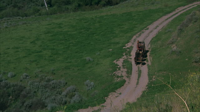 vidéos et rushes de wide high angle down of grass on hills, curved trails from right to center. six-horse drawn carriage  on trail. shot follows carriage approaching bottom left. - voiture attelée