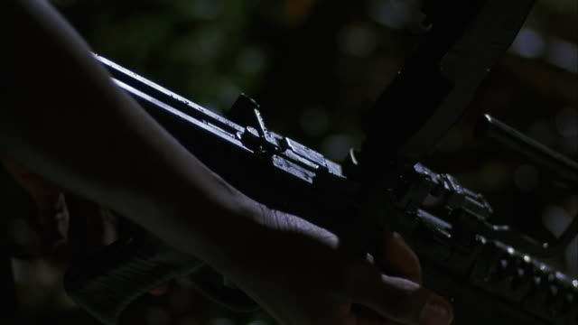 close angle of hands loading machine gun with bandolier of bullets. insert. - bandolier stock videos & royalty-free footage