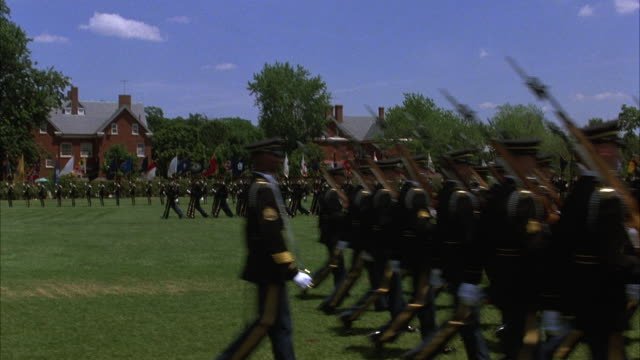 close angle of soldiers in military ceremony or presentation of colors at military academy in fort meyers, military building and trees in background. line of soldiers in front marching across to right. soldiers in dark uniforms with rifles on right should - marching stock videos and b-roll footage