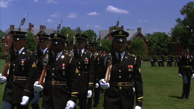 medium angle of soldiers in military ceremony or presentation of colors at military academy in fort meyers, military building and trees in background. line of soldiers on left approaching front, turns right and marches across to right. soldiers in dark un - 1987 stock videos & royalty-free footage