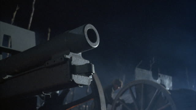 medium angle of cannon, world war i soldiers in background. see reflections of explosions on bottom of cannon. explosions. - artillery stock videos & royalty-free footage