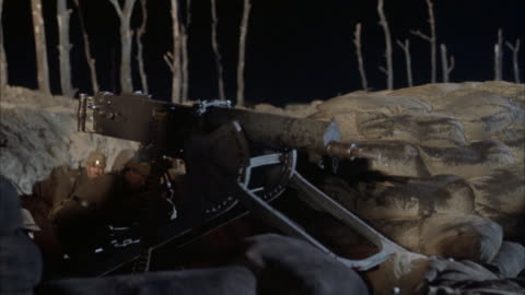 medium angle of machine gun by trench during world war i. soldiers in trenches stand up, one begins loading bandolier into machine gun while another fires gun. flashes in frame from artillery. - world war one stock videos & royalty-free footage