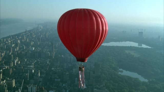 vídeos de stock e filmes b-roll de aerial of red hot air balloon floating over manhattan, see new york skyline and central park, sun halations. - balão de ar quente